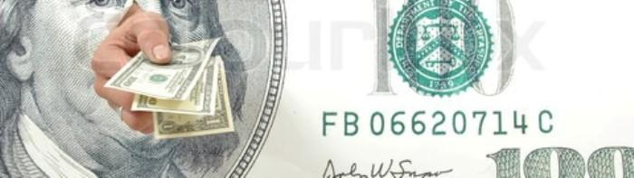 Hand holding hundred dollar bills through a large hundred dollar bill